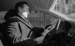 Homem de negócios que lê um jornal no carro, exterior, dia imagens de stock royalty free