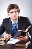Homem de negócios que lê um livro e uma escrita Foto de Stock