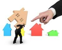 Homem de negócios que leva a casa de madeira com o dedo indicador grande que aponta a foto de stock