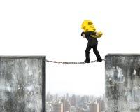 Homem de negócios que leva o euro- sinal dourado que equilibra na corrente oxidada Fotografia de Stock Royalty Free