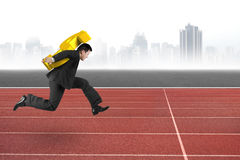 Homem de negócios que leva o sinal de dólar dourado que corre na trilha Fotos de Stock