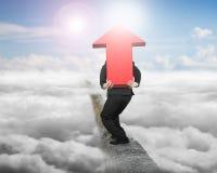 Homem de negócios que leva o sinal vermelho da seta no cume com nuvem da luz solar Foto de Stock Royalty Free