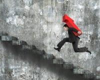 Homem de negócios que leva o sinal vermelho da seta que corre em escadas imagem de stock