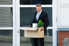 Homem de negócios que leva seus pertences na caixa após o incêndio Foto de Stock