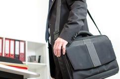 Homem de negócios que leva sua mala de viagem do portátil em seu ombro Imagens de Stock Royalty Free