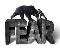 Homem de negócios que luta contra o urso preto na palavra do concreto do medo 3d Imagem de Stock