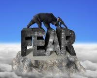 Homem de negócios que luta contra o urso preto na palavra do concreto do medo 3d Fotografia de Stock
