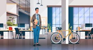 Homem de negócios que mantém o escritório criativo do portátil que coworking a bicicleta moderna interior da mesa do local de tra ilustração royalty free