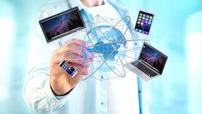 Homem de negócios que mantém um computador e os dispositivos indicados em um futuri Foto de Stock