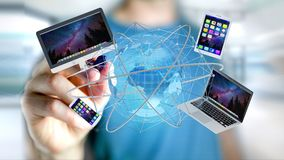 Homem de negócios que mantém um computador e os dispositivos indicados em um futuri Fotografia de Stock Royalty Free