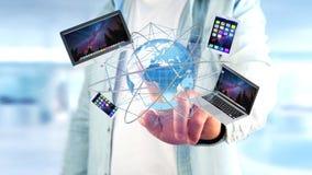 Homem de negócios que mantém um computador e os dispositivos indicados em um futuri Imagens de Stock Royalty Free