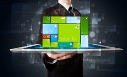 Homem de negócios que mantem uma tabuleta com software moderno operacional  Imagens de Stock Royalty Free