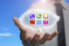 Homem de negócios que mostra ícones coloridos do app na nuvem com céu da natureza Fotos de Stock