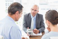 Homem de negócios que mostra a calculadora a seus clientes Imagem de Stock Royalty Free