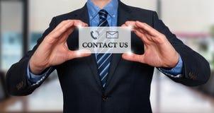 Homem de negócios que mostra a cartão com contato nos texto Imagem de Stock
