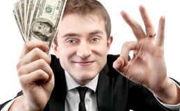 Homem de negócios que mostra o fã da APROVAÇÃO do dinheiro e do sinal Fotografia de Stock Royalty Free