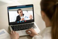 Homem de negócios que mostra o relatório financeiro positivo através da chamada video imagem de stock royalty free
