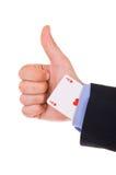 Homem de negócios que mostra o sinal aprovado com o cartão do ás sob a luva. Fotos de Stock
