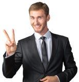 Homem de negócios que mostra o sinal da vitória fotografia de stock