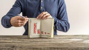 Homem de negócios que mostra seu caderno com gráficos financeiros imagem de stock