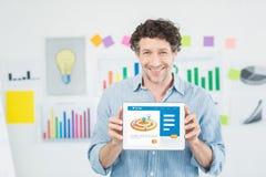 Homem de negócios que mostra a tabuleta 3d digital com a tela vazia no escritório criativo Imagens de Stock