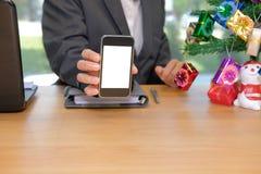 homem de negócios que mostra a tela do telefone esperto durante o Natal y novo imagens de stock