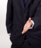 Homem de negócios que mostra um aperto de mão à câmera Fotografia de Stock Royalty Free