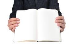 Homem de negócios que mostra um caderno com páginas vazias foto de stock