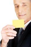 Homem de negócios que mostra um cartão de nome amarelo da identidade Imagem de Stock Royalty Free