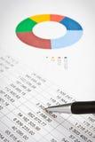 Homem de negócios que mostra um diagrama em um relatório financeiro usando uma pena fotos de stock