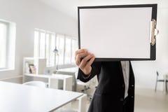 Homem de negócios que mostra um pedaço de papel vazio em uma prancheta imagens de stock