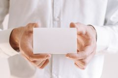 Homem de negócios que mostra um pedaço de papel vazio Homem de negócios na camisa branca que dá o cartão fotografia de stock
