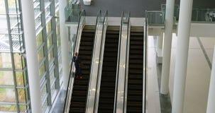 Homem de negócios que move-se para baixo da escada rolante 4k video estoque