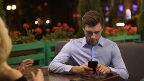 Homem de negócios que não paga a atenção a sua amiga falador, viciado ao dispositivo video estoque