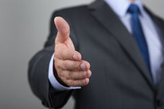 Homem de negócios que oferece sua mão para o aperto de mão Fotos de Stock Royalty Free