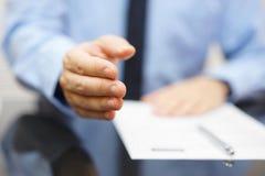 Homem de negócios que oferece um aperto de mão e um contrato Fotografia de Stock Royalty Free