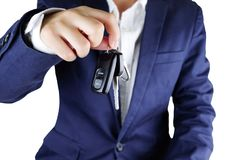 Homem de negócios que oferece uma chave do carro, fim acima da mão que mostra a chave da imagens de stock