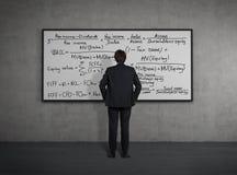 Homem de negócios que olha às fórmulas Fotos de Stock