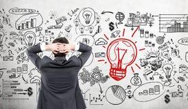 Homem de negócios que olha ícones startup e o esboço vermelho da ampola Fotos de Stock