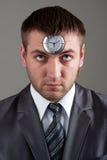 Homem de negócios que olha ao pulso de disparo na cabeça Foto de Stock Royalty Free