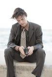 Homem de negócios que olha através de sua carteira fotografia de stock