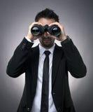 Homem de negócios que olha através dos binóculos Fotos de Stock
