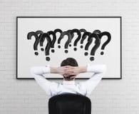 Homem de negócios que olha em pontos de interrogação imagem de stock royalty free