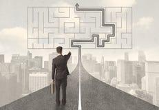Homem de negócios que olha a estrada com labirinto e solução Fotos de Stock Royalty Free