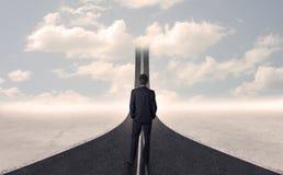 Homem de negócios que olha a estrada 3d que vai acima no céu Foto de Stock Royalty Free
