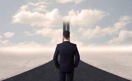 Homem de negócios que olha a estrada 3d que vai acima no céu Imagens de Stock