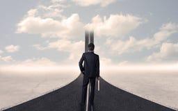 Homem de negócios que olha a estrada 3d que vai acima no céu Imagem de Stock Royalty Free