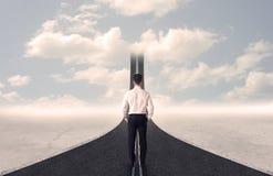 Homem de negócios que olha a estrada 3d que vai acima no céu Imagem de Stock