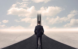 Homem de negócios que olha a estrada 3d que vai acima no céu Fotografia de Stock Royalty Free
