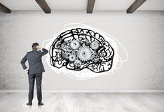 Homem de negócios que olha o cérebro com rodas denteadas Imagem de Stock Royalty Free
